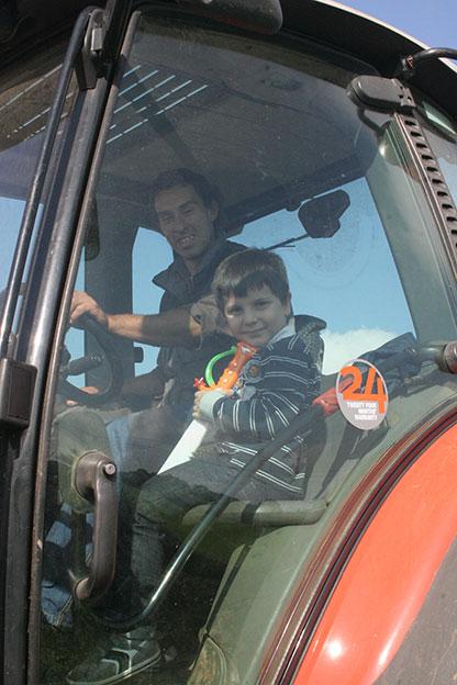 Agriturismo Siracusa con animali: Pietro Spanò e il piccolo Michele Lombardo a bordo di un mezzo agricolo della masseria Italia