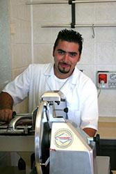 Agriturismo Siracusa: Santo Italia, il responsabile della macelleria alle prese con l'affettatrice mentre serve un cliente della macelleria aziendale