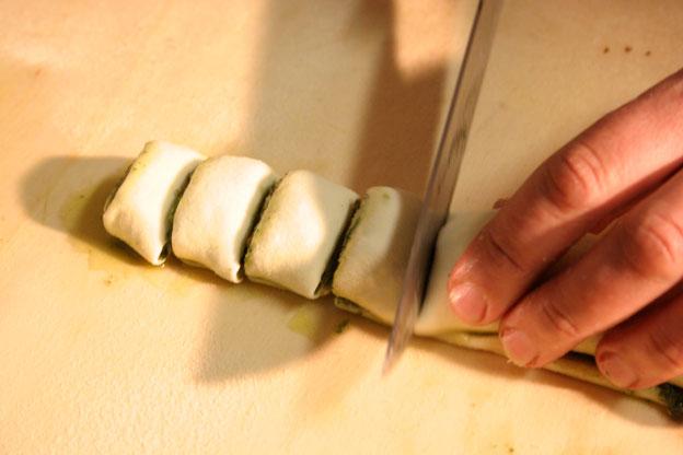 Ristorante a Siracusa: il taglio del cordone di pasta di casa attorcigliato attorno allo strato di pesto di nepitella